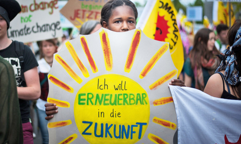 woman holds renewable energy sign