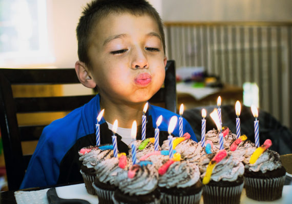 boy blows out candles
