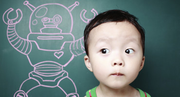 child beside a chalkboard robot