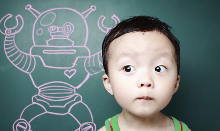 child beside a chalkboard robot