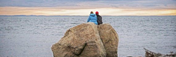 two people sitting on a large rock