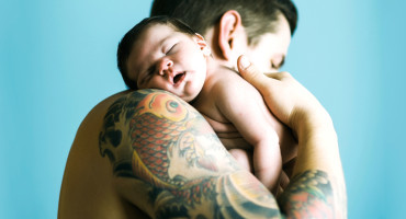 tattooed dad holds newborn baby