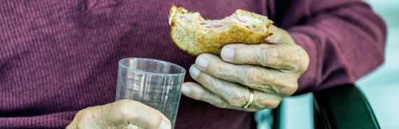elderly man with sandwich and juice