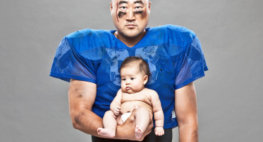 football player holds baby