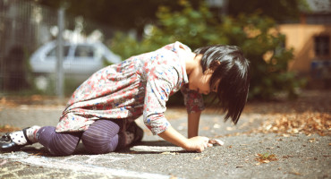 little girl drawing with chalk