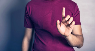man in purple shirt gestures with hand