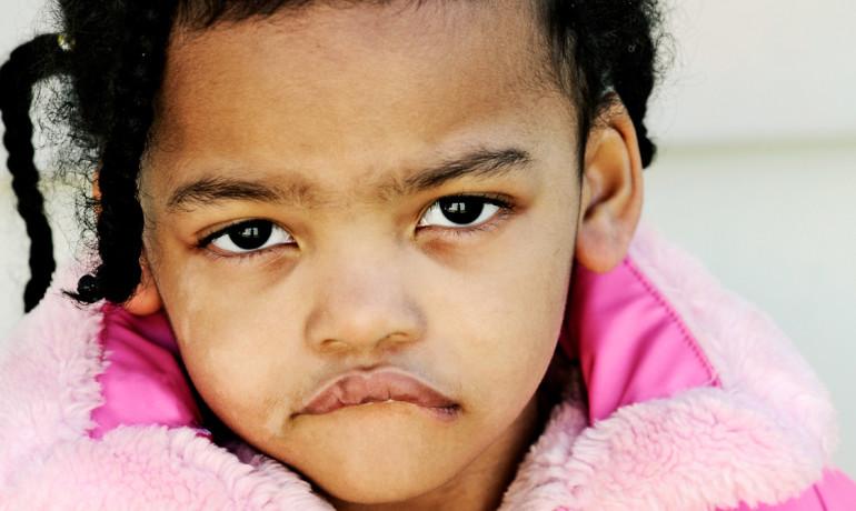 sad little girl in pink coat
