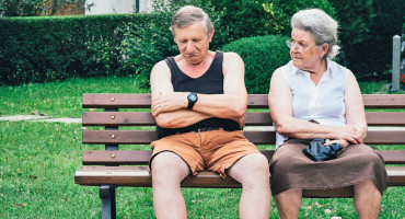 older man sleep on bench with wife