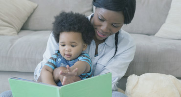 mom reads book to baby