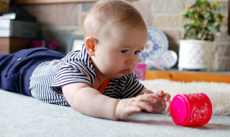 baby reaches for a cup