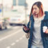 woman walking while checking phone