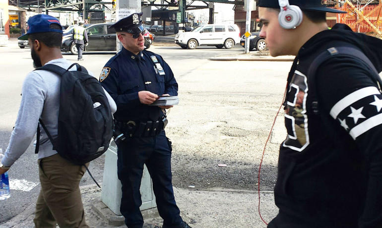 police officer hands out information sheets to pedestrians