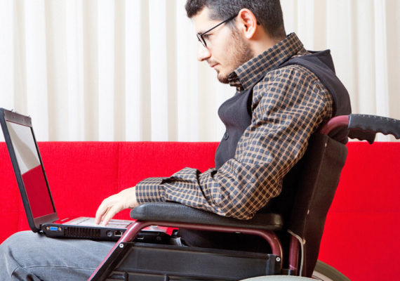 man uses wheelchair & laptop