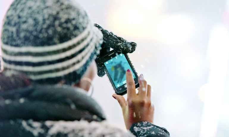 woman using a phone in a blizzard