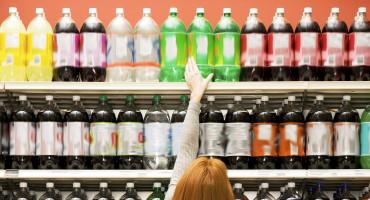 Shopper reaching for soda in aisle in supermarket