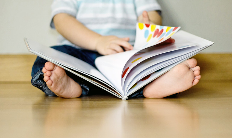 toddler reads a book