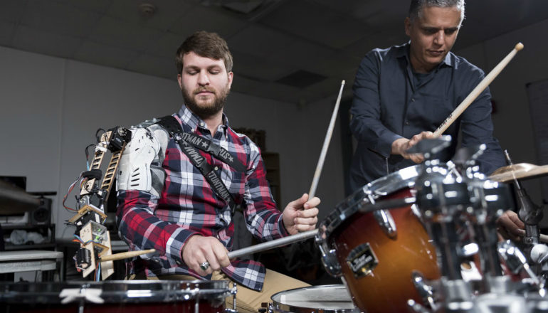 man wears robotic arm and plays the drums