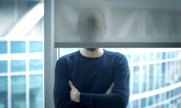 man's face hidden behind a window blind