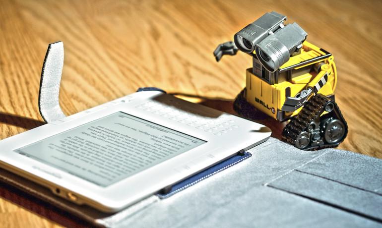 Toy Wall-E robot reading an E-book.