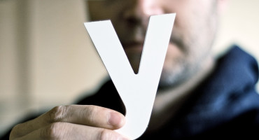 guy holding a letter Y