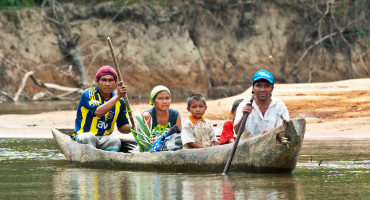 family paddles a dugout canoe