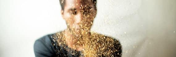 man throws glitter into the air