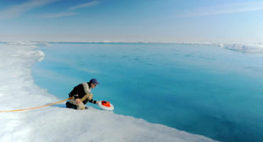 """This study does a good job of pinning down the fact that the [Arctic sea] ice is disappearing for a whole bunch of reasons—and that is causing the surface of Greenland's melt area to increase,"" says Jennifer Francis. Above: A scientist deploys an autonomous drift boat equipped with several sensors in a meltwater river on the surface of the Greenland ice sheet on July 19, 2015. (Credit: NASA/Goddard/Jefferson Beck via Flickr)"