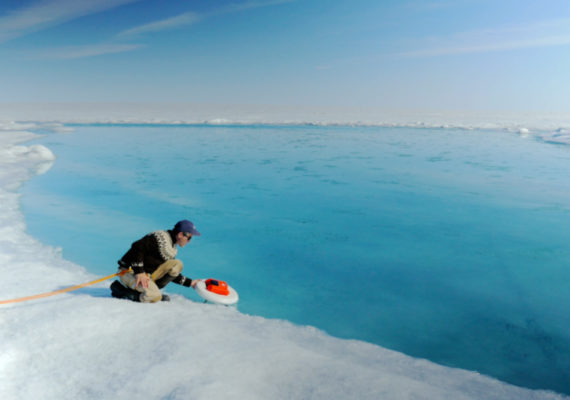 """""""This study does a good job of pinning down the fact that the [Arctic sea] ice is disappearing for a whole bunch of reasons—and that is causing the surface of Greenland's melt area to increase,"""" says Jennifer Francis. Above: A scientist deploys an autonomous drift boat equipped with several sensors in a meltwater river on the surface of the Greenland ice sheet on July 19, 2015. (Credit: NASA/Goddard/Jefferson Beck via Flickr)"""