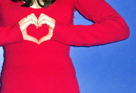woman makes heart with hands