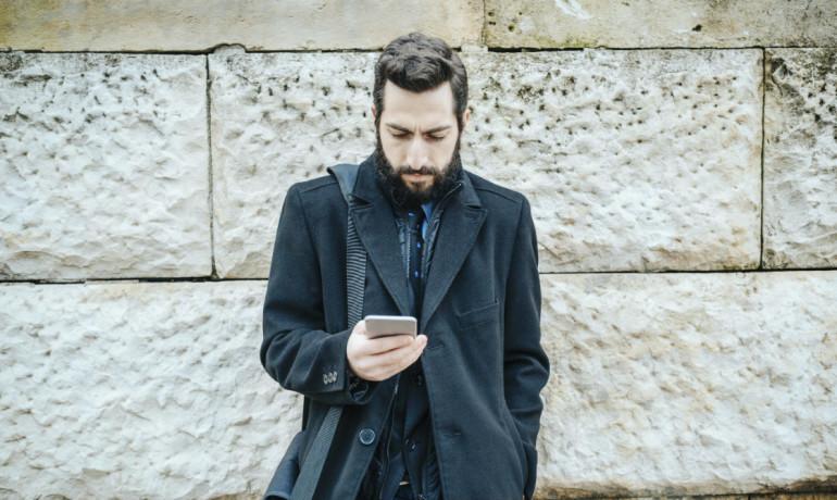 man staring at his phone