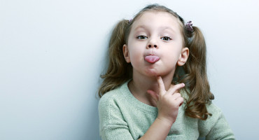 little girl sticks out tongue