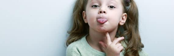 little girl sticks out tongue