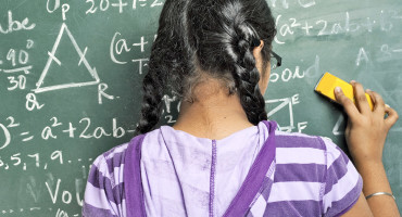 girl erasing math on a chalkboard