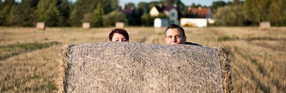 farmers behind hay bale