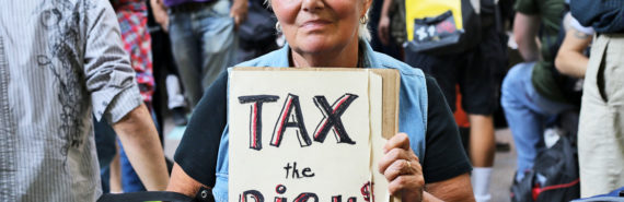 woman holds tax the rich sign
