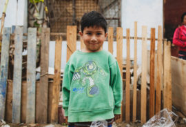 boy in front of fence