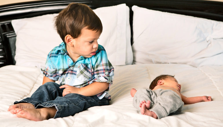 toddler looks at newborn baby