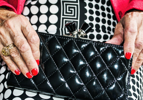 older woman holds purse