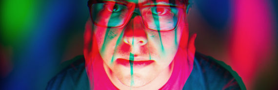 pink and green hands over face