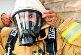 man puts on firefighter mask