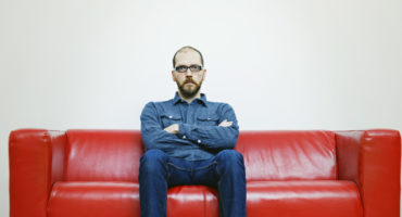 man sits on red couch
