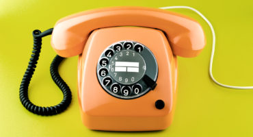 orange rotary phone on green