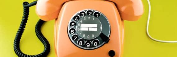 orange rotary phone on green