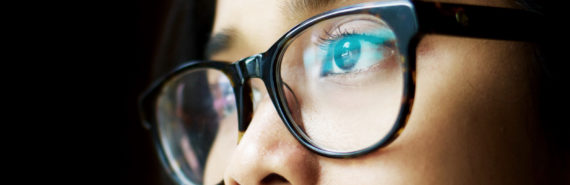 screen reflects in woman's glasses