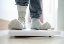 person in socks stands on bathroom scale