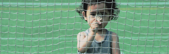 child hides behind a net