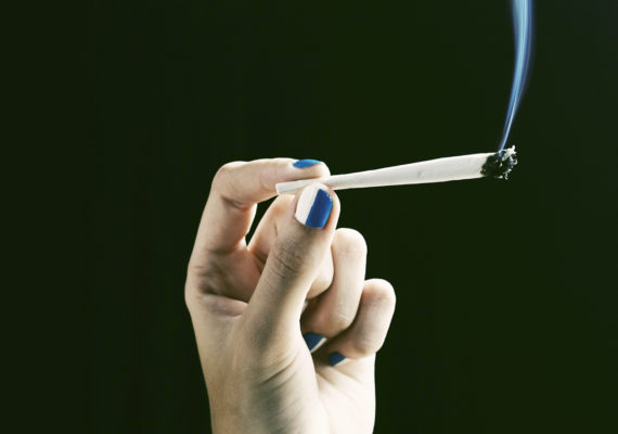 woman holds a joint