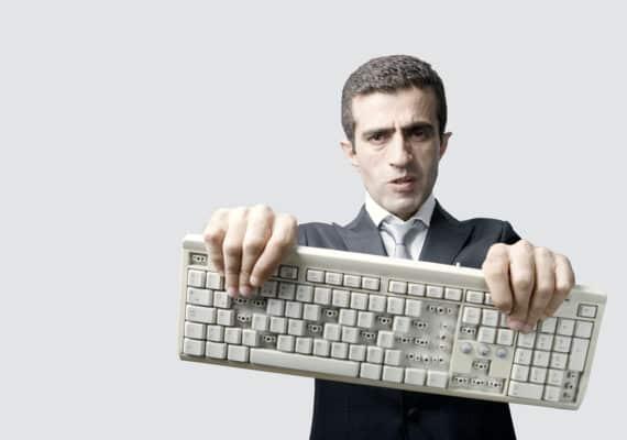 man holds a broken keyboard