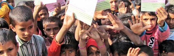 kids in India hold vaccination cards