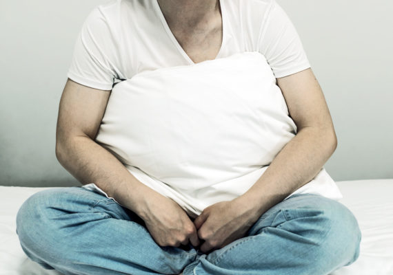 man holds pillow on his lap